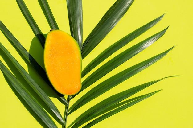 Mango maduro medio cortado en hojas de palmeras tropicales sobre superficie verde