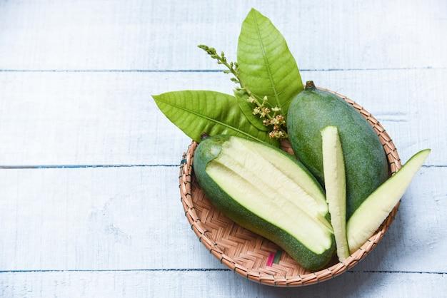 Mango verde fresco y canasta de hojas verdes.