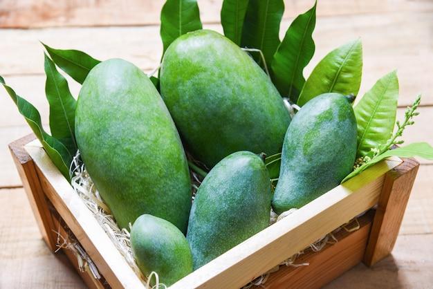 Mango verde fresco y hojas verdes en la vista superior de la caja de madera