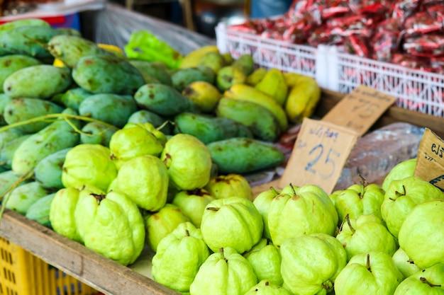 Mango verde y frutas frescas en mesa en mercado fresco