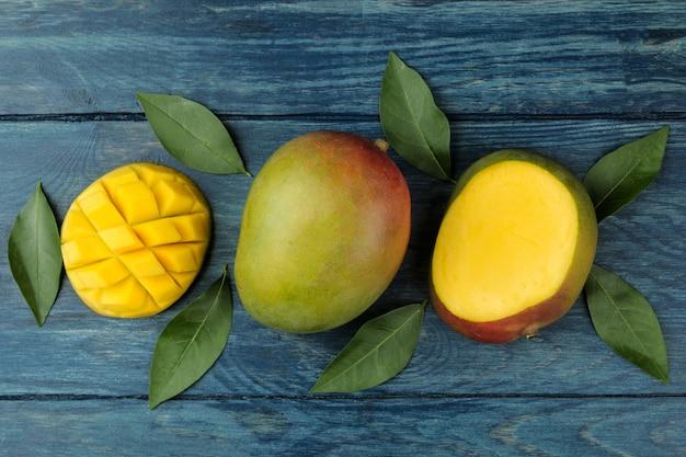 Mangos frescos maduros de fruta y rodajas y hojas sobre una mesa de madera azul