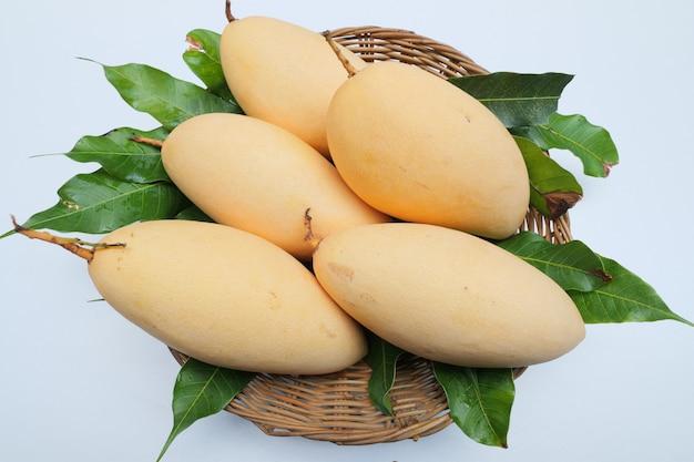 Mangos maduros en canasta con hojas.