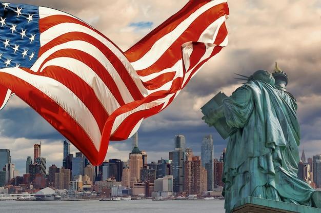 Manhattan, ciudad de nueva york en la estatua de la libertad, la bandera estadounidense en ee.
