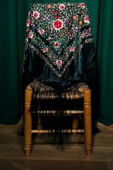 Mania chal en una silla de madera
