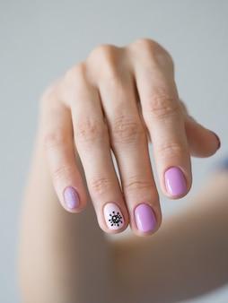 Manicura creativa con coronavirus pintado en las uñas.