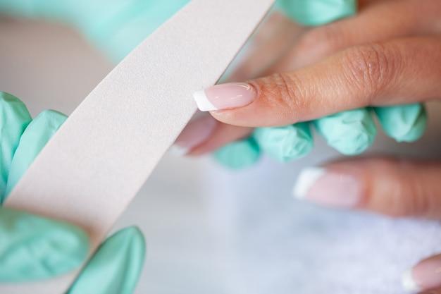 Manicura. maestro de uñas haciendo manicura en estudio de belleza