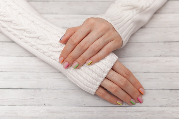 Manicura moderna multicolor, diseño de uñas, estado de ánimo de verano, manos en un suéter blanco