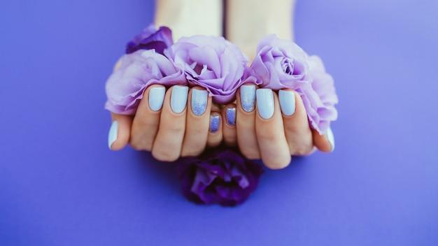 Manicura morada sobre un fondo liso con flores.