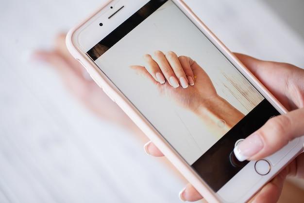 Manicura. una mujer toma una fotografía de la mano de uñas de manicura