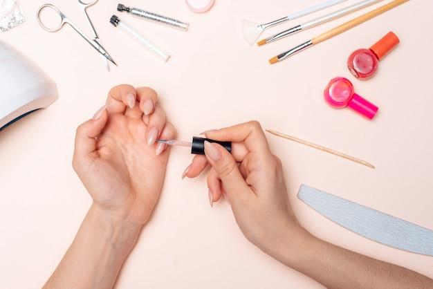 Manicura. una niña se pinta las uñas. manos cerca