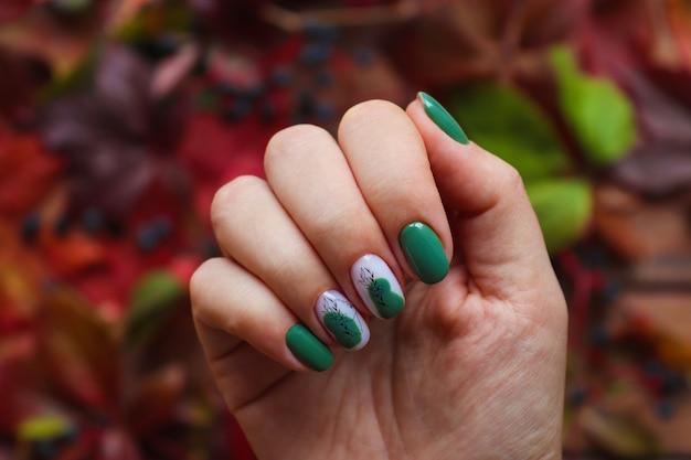 Manicura de otoño. uñas de pistacho cuidadas con esmalte de gel sobre fondo de hojas de otoño