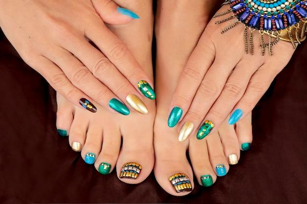 Manicura y pedicura con esmalte de uñas color turquesa con pedrería