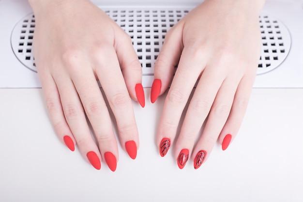 Manicura roja con un patrón. manos femeninas en salón de manicura