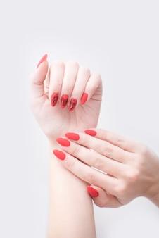 Manicura roja con un patrón. manos femeninas sobre un fondo blanco