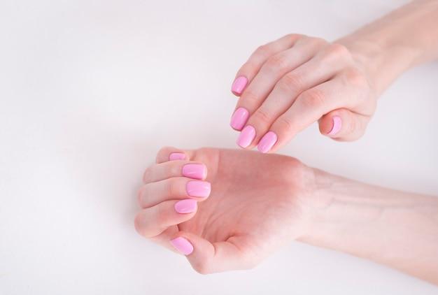 Manicura rosa suave en manos femeninas