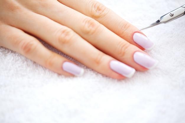 Manicura spa. manicura francesa en el salón de spa. manos de mujer en un salón de manicura recibiendo un procedimiento de manicura. procedimiento de manicura