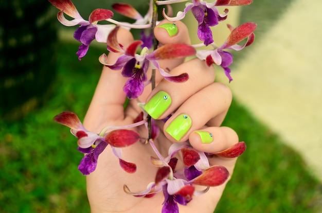 Manicura verde con hermosas flores de orquídeas