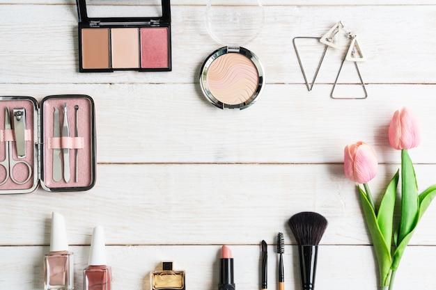 Manicure los instrumentos y las herramientas en caja rosada con el esmalte de uñas, el cosmético y los accesorios de las mujeres en el fondo de madera blanco, visión superior, copia spce, concepto de la belleza.