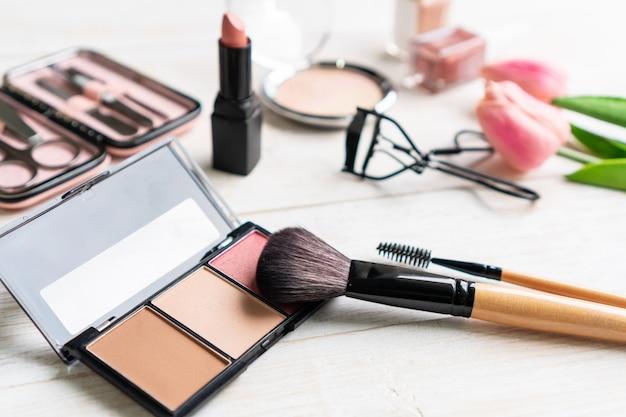 Manicure los instrumentos y las herramientas en caja rosada con el esmalte de uñas, el cosmético y los accesorios de las mujeres en la tabla de madera blanca, cierre para arriba, concepto de la belleza.
