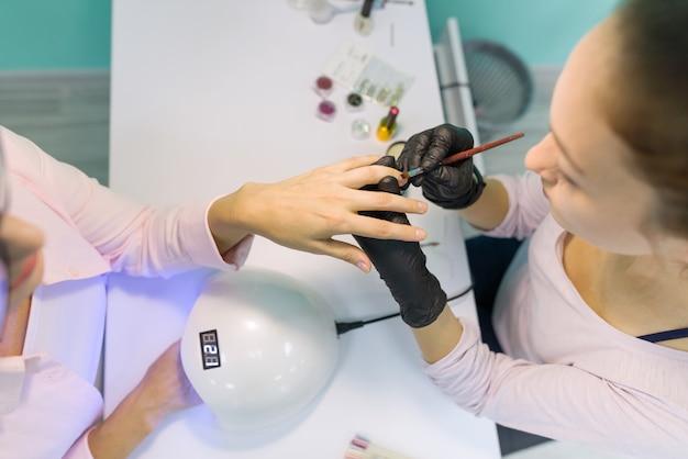 Manicurist utiliza una lámpara ultravioleta para fijar el esmalte de uñas en gel.