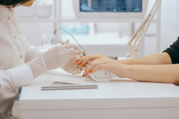Manicurista hace manicura