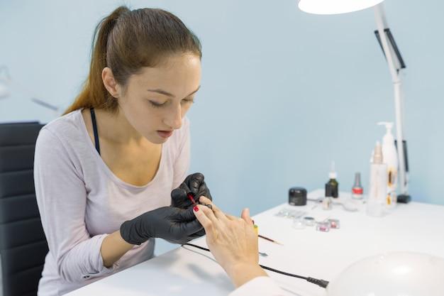 Manicurista haciendo manicure profesional