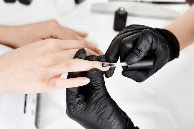 Manicurista profesional en guantes aplicando capa base en el dedo anular.