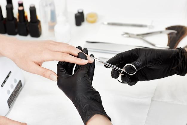 Manicurista profesional en guantes negros cortando cutícula con tijeras de manicura.