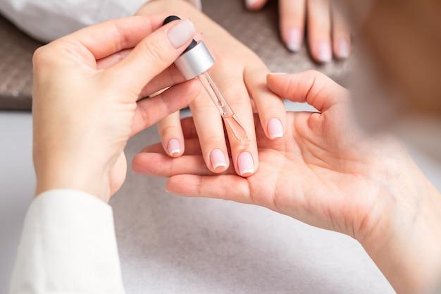 Manicurista vierte aceite en uñas de mujer