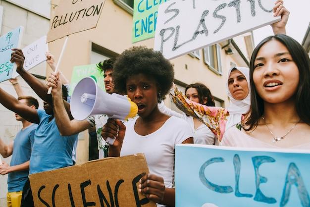 Manifestación pública en la calle contra el calentamiento global y la contaminación. grupo de personas multiétnicas que protesta por el cambio climático y los problemas plásticos en los océanos.