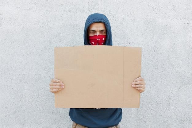 Manifestante decepcionado serio con pañuelo en la cara y cartón
