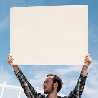 Manifestante sosteniendo el tablero con maqueta para demostración