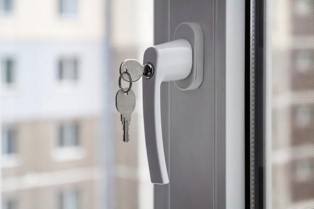 Manija con cerradura y llave en la ventana de pvc. edificio de apartamentos en el fondo. primer plano, enfoque selectivo