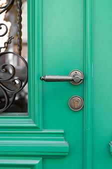 Manija decorativa vintage antigua y cerradura en puerta de madera verde.