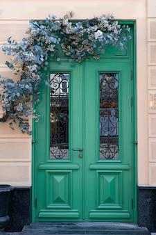 Manija decorativa vintage antiguo y cerradura en una puerta de madera verde