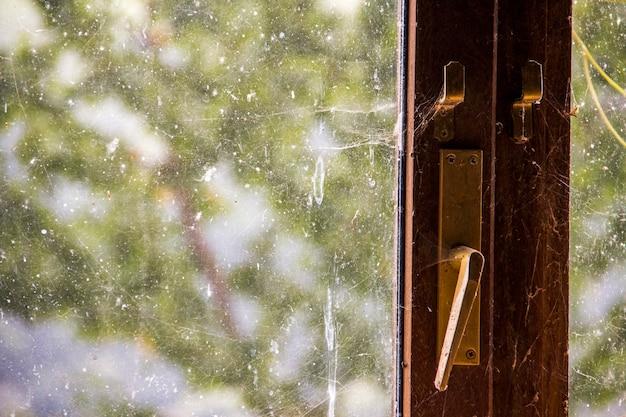Manija de ventana vieja con telas de araña y vidrio sucio concepto vintage