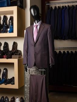 Un maniquí con un traje clásico de hombre con el telón de fondo de estantes con ropa y zapatos. elegante y con estilo. disposición vertical. moda italiana