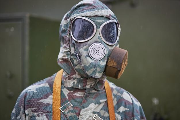 Maniquí vestido con un traje especial de camuflaje y máscara antigás
