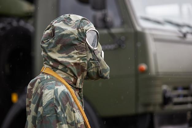 Maniquí vestido con un traje especial de protección química de camuflaje y soportes de máscara de gas de un camión militar
