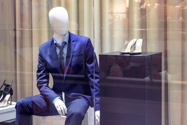 Maniquíes en la ventana de la tienda de ropa elegante estilo de moda