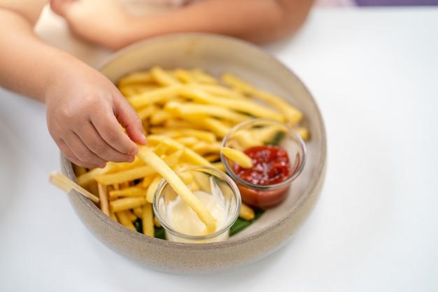 Manita sosteniendo papas fritas sumergidas en salsa de mayonesa