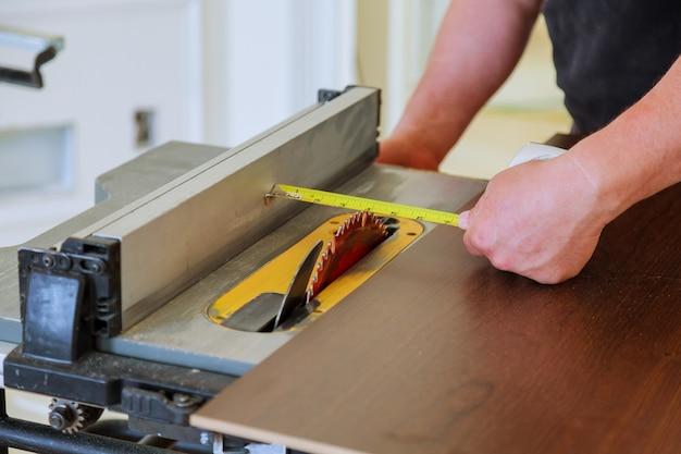 Manitas irreconocibles cortando madera sierra circular en la nueva casa