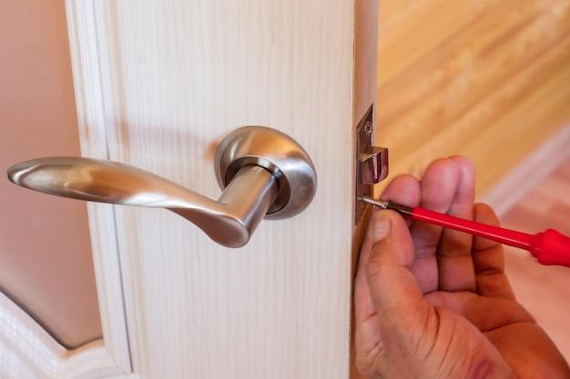 Manitas repara la cerradura de la puerta en la habitación, hombre fijando la cerradura con destornillador, primer plano de la puerta de reparación, instalación de cerrajero profesional.