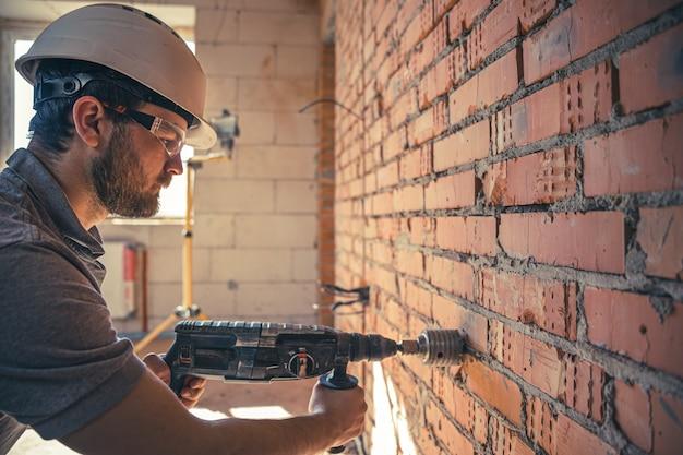 Manitas en un sitio de construcción en el proceso de perforación de una pared con un perforador.
