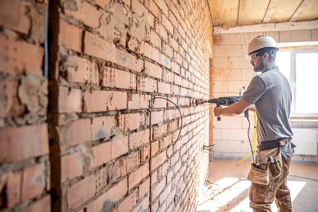 Manitas en un sitio de construcción en el proceso de perforación de una pared con un perforador