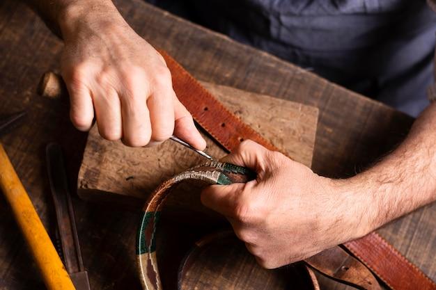 Manitas trabajando en un cinturón de cuero