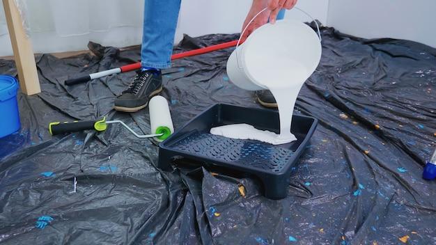 Manitas vertiendo pintura blanca para la renovación del hogar. pareja en piso, reparación y cambio de imagen