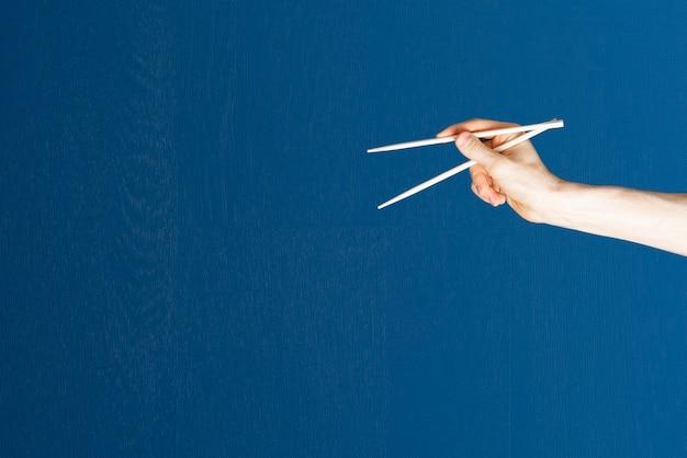La mano abstracta que sostiene el par vacío de palillos de madera aislado sobre fondo de color,