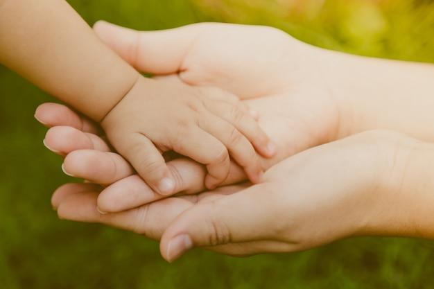 Mano de adulto agarrando mano de un bebé