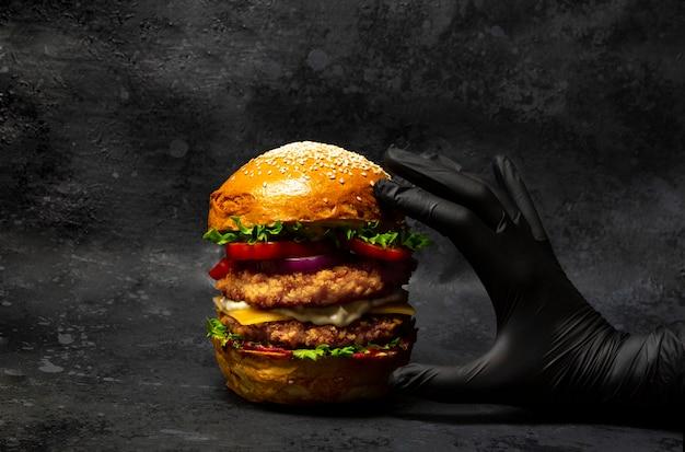 Mano agarrando una gran hamburguesa doble de pollo con queso y verduras